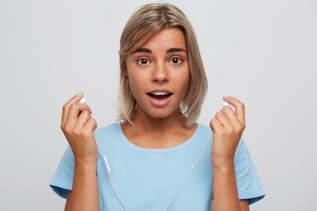 Zbliżenie uśmiechnięta zaskoczona młoda kobieta o blond włosach