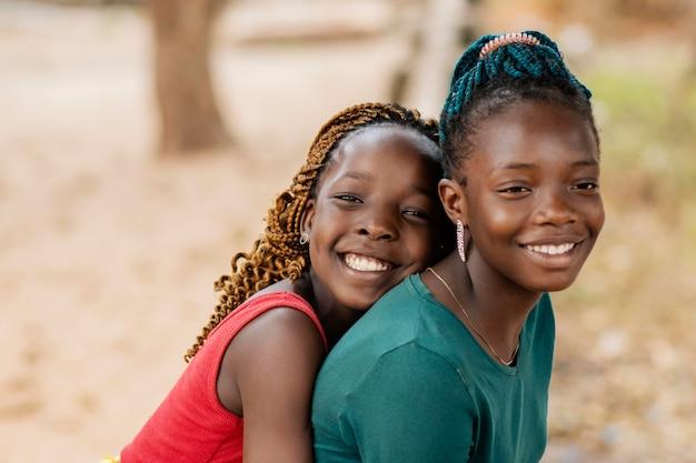 Zbliżenie uśmiechnięte afrykańskie dziewczyny na zewnątrz