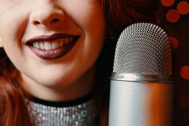 Zbliżenie uśmiechnięte śpiewaczki i mikrofon retro na bokeh rozmycie tła redhaired wesoły w...