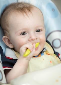 Zbliżenie uśmiechniętego chłopca jedzącego owsiankę z łyżki