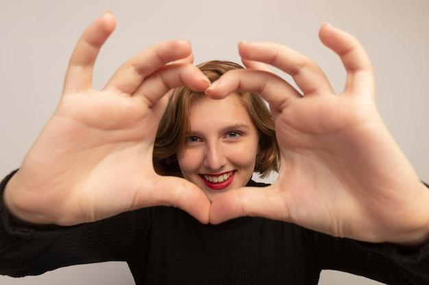 Zbliżenie uśmiechniętej młodej kobiety blondynki patrzącej na przód robi znak serca na białym tle na białej ścianie