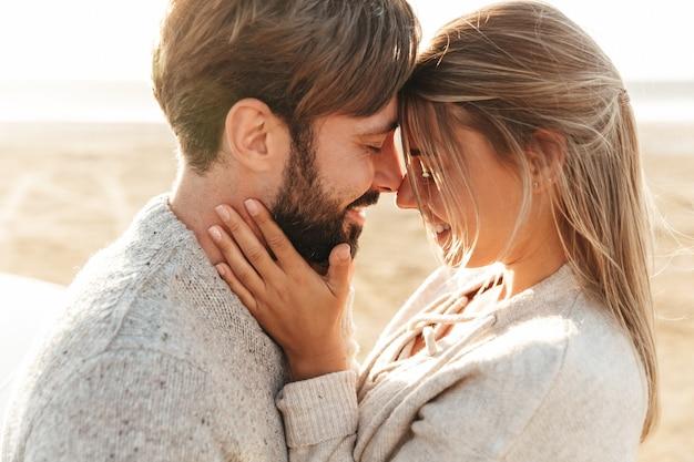 Zbliżenie uśmiechniętej pięknej młodej pary obejmującej się, stojąc na plaży
