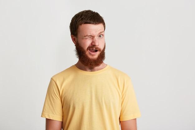 Zbliżenie uśmiechnięty atrakcyjny młody człowiek hipster z brodą nosi koszulkę i mruga