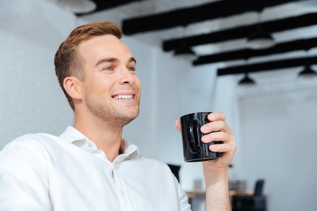Zbliżenie uśmiechnięty młody biznesmen siedzi i pije kawę w biurze