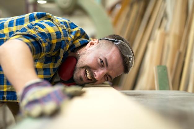 Zbliżenie uśmiechnięty pracownik stolarza sprawdzanie jakości i gładkości wyrobów z drewna w warsztacie stolarskim.