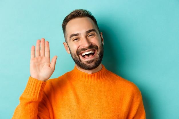 Zbliżenie: uśmiechnięty przyjazny młody mężczyzna, machający ręką, by się przywitać, witając, stojąc na jasnoniebieskim tle.