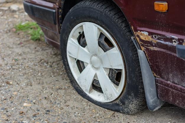 Zbliżenie uszkodzonej opony. wyciek z koła samochodu. przebita opona w terenie czeka na naprawę.