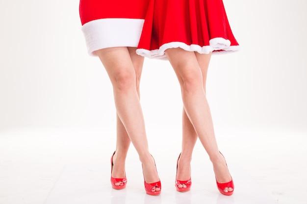 Zbliżenie uwodzicielskich kobiecych nóg w czerwonych sukienkach świętego mikołaja i czerwonych butach na wysokim obcasie izolowanych na białym tle