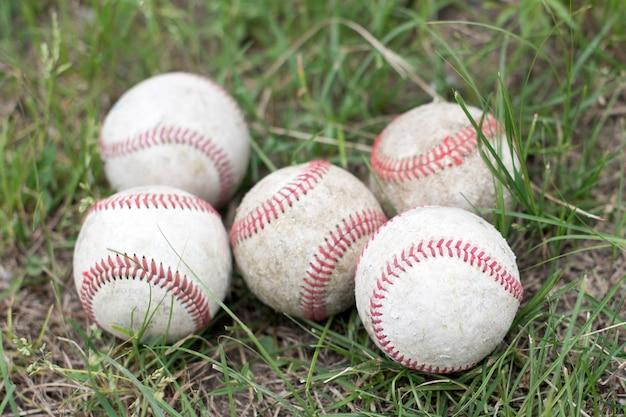 Zbliżenie używane piłki do baseballu na zielonej trawie dziedzinie sportu koncepcji