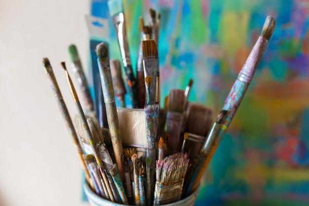 Zbliżenie używanych pędzli artysty w szklance
