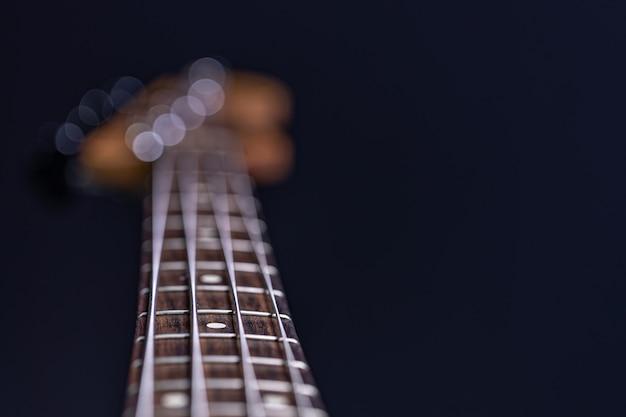 Zbliżenie w centrum uwagi strun na gitarze basowej na niewyraźnym czarnym tle.
