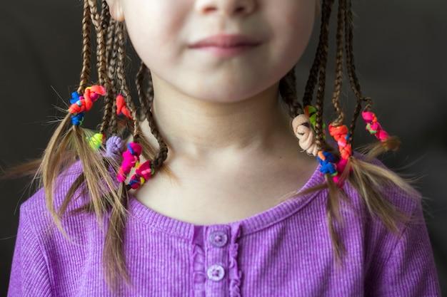 Zbliżenie warkocz włosów dziewczynki z kolorowe gumki
