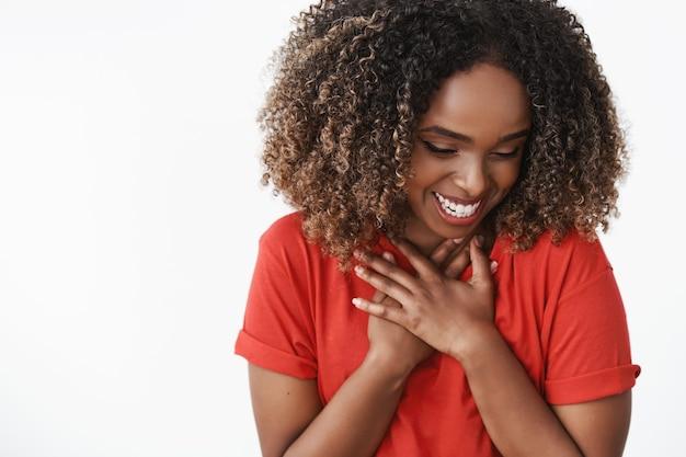 Zbliżenie wdzięcznej i zaskoczonej słodkiej kobiety otwartego prezentu walentynkowego zdumionej i wdzięcznej prasy dłoni do zginania klatki piersiowej i śmiejącej się ze zdumienia i szczęścia, uśmiechając się nieśmiało