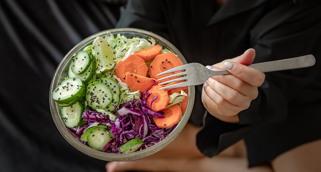 Zbliżenie wegetariańskie sałatki ze świeżych warzyw w rękach kobiet.