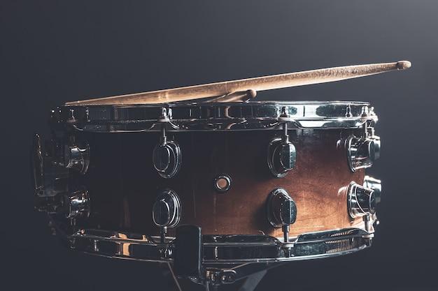 Zbliżenie, werbel, instrument perkusyjny na ciemnym tle z oświetleniem scenicznym.