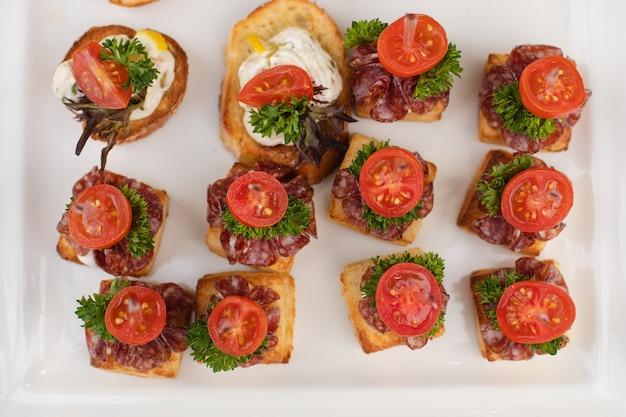 Zbliżenie wesele z pysznymi kanapkami i kanapkami z kiełbasą, pietruszką i pomidorami z twarogiem. kanapki na białych płytach ceramicznych na weselu.