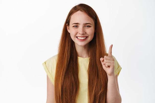 Zbliżenie wesoła młoda kobieta z rudymi włosami i białym uśmiechem, wskazując palcem w górę stojący w t-shirt na białym tle.