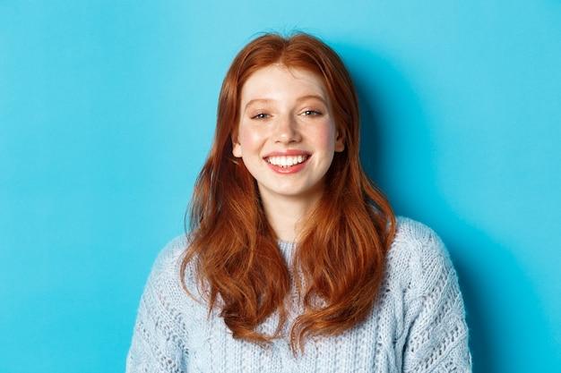 Zbliżenie: wesoła nastolatka z rudymi kręconymi włosami, uśmiechnięta szczęśliwa do kamery, stojąca na niebieskim tle.