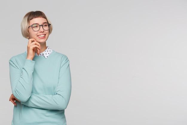 Zbliżenie wesoła piękna młoda kobieta nosi niebieską bluzę