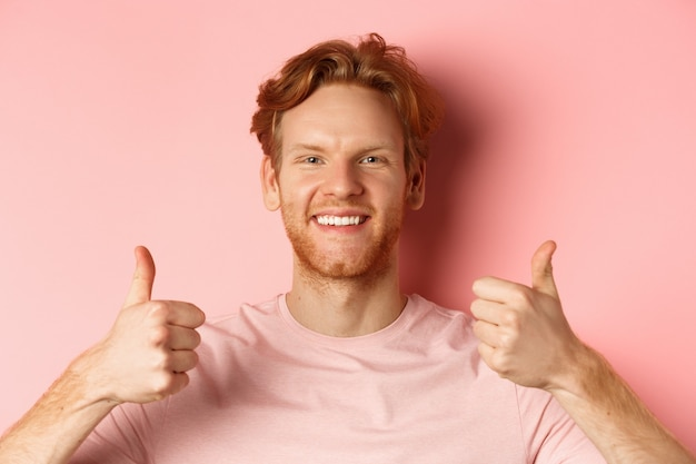 Zbliżenie wesołego mężczyzny z rudymi włosami i brodą, pokazującego kciuki do góry i uśmiechającego się, mówiącego tak, aprobuj i chwal coś fajnego, stojącego na różowym tle.