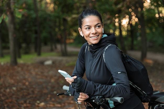 Zbliżenie wesoły młoda kobieta fitness, jazda na rowerze w parku, słuchanie muzyki przez słuchawki, trzymając telefon komórkowy