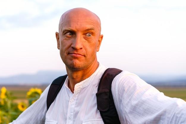 Zbliżenie wesoły młody człowiek w białej koszulce z plecakiem stoi i uśmiecha się w polu słoneczników ładny kaukaski łysy mężczyzna na zewnątrz podczas zachodu słońca
