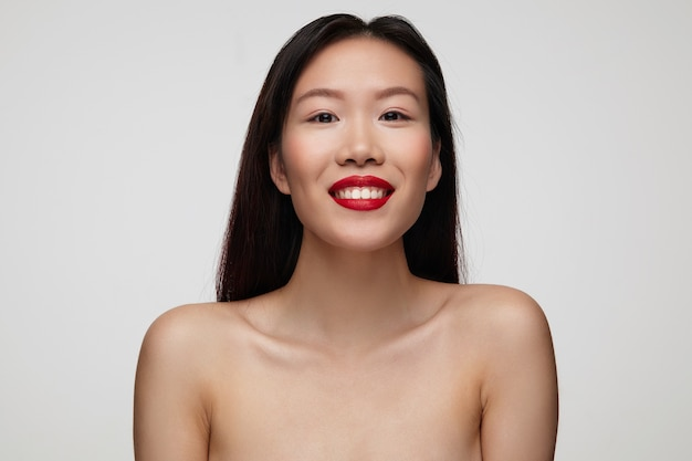 Zbliżenie wesoły młody piękny brunetka kobieta z czerwonymi ustami, szczęśliwie patrząc i uśmiechając się szeroko, będąc w miłym nastroju podczas pozowania na białej ścianie