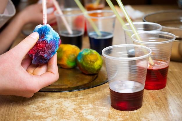 Zbliżenie wideo przedstawiające ręce dzieci przy użyciu barwnika i malowanie na białych jajkach na twardo podczas przygotowań do wielkanocy