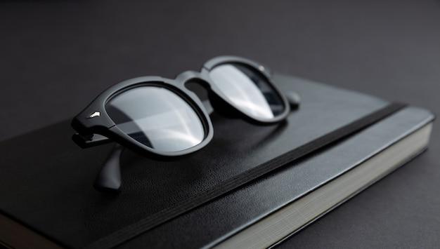Zbliżenie widok czarni eyeglasses na modnym notatniku