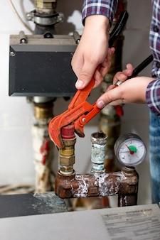 Zbliżenie widok hydraulika obracającego zawór systemu ogrzewania za pomocą czerwonych szczypiec