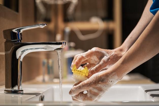 Zbliżenie widok kobiety myje jej ręki z mydłem i muśnięciem