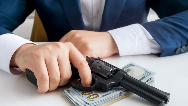 Zbliżenie widok męskiego biznesmena lub przestępcy trzymającego pistolet na zwitek gotówki