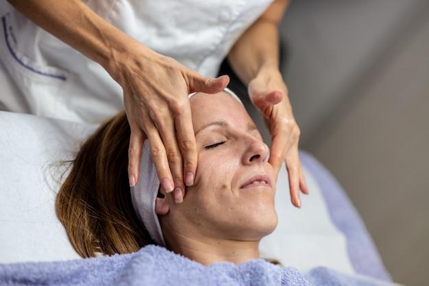 Zbliżenie widok młodej kobiety coraz odmładzający masaż twarzy przez lekarza.