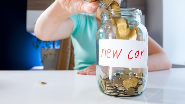 Zbliżenie widok młodej kobiety zbierając pieniądze na zakup nowego samochodu. koncepcja inwestycji finansowych, wzrostu gospodarczego i oszczędności bankowych.
