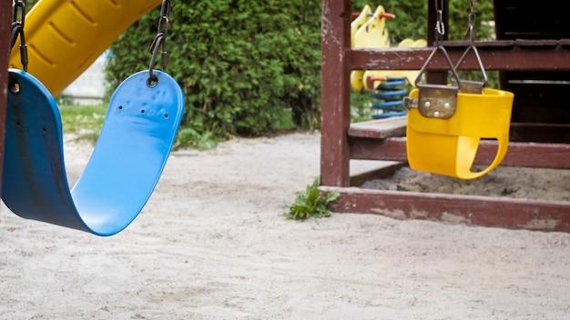 Zbliżenie widok pustych huśtawek na placu zabaw w parku z powodu samoizolacji i pandemii koronawirusa.