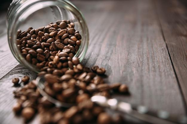Zbliżenie widok szklany słój z rozlewać kawowymi fasolami na drewnianym stole