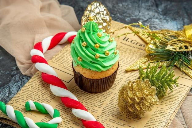 Zbliżenie widok z dołu mini ciastko świąteczne cukierki świąteczne ozdoby na gazetowym beżowym szalu na ciemnym
