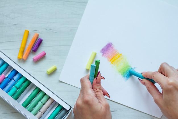 Zbliżenie widok z góry kobiece ręce rysunek wielobarwny kredki na białym prześcieradle