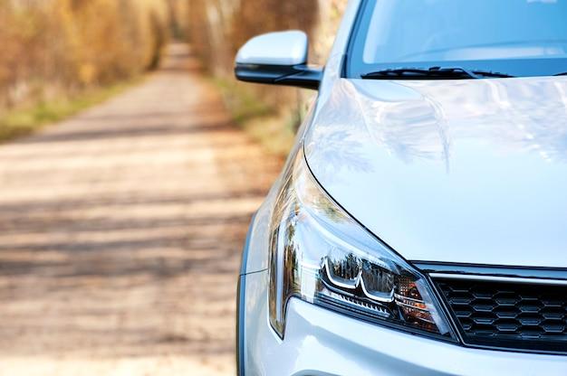 Zbliżenie widok z przodu samochodu na tle jesiennej leśnej drogi szklany reflektor tło