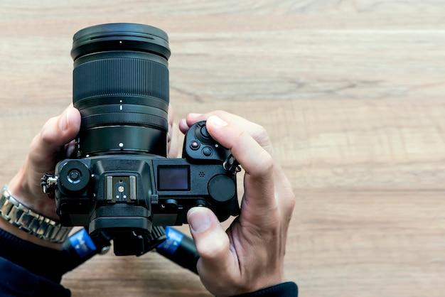 Zbliżenie widoku ręka trzyma cyfrową kamerę z drewnianym tłem.