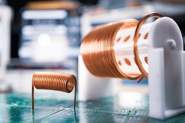 Zbliżenie wiele motków skręconego drutu miedzianego stoi na zielonym mikroukładzie. koncepcja fabryczna do produkcji potężnego obwodu oscylacyjnego i komponentów o wysokiej częstotliwości
