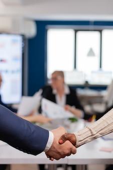 Zbliżenie wielorasowych partnerów biznesowych stojących przed biurkiem konferencyjnym, ściskając ręce po podpisaniu umowy partnerskiej partnership