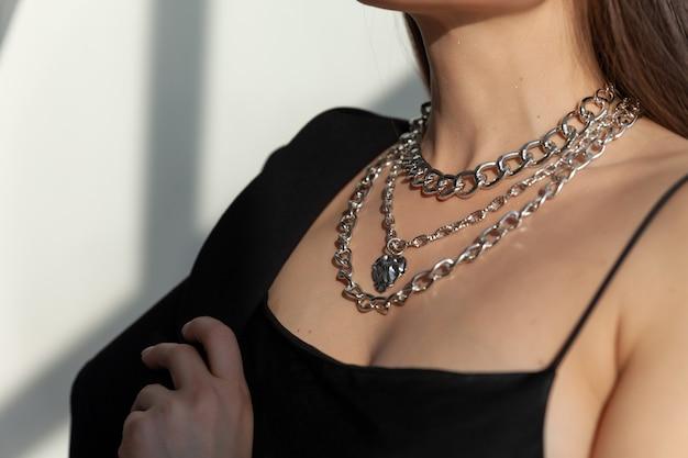 Zbliżenie wielu nowoczesnych srebrnych łańcuchów z zawieszką w kształcie serca na modelowej brunetce z długimi włosami, metalowym naszyjnikiem, światłem słonecznym