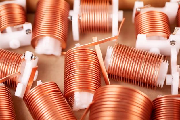 Zbliżenie wielu skręconych płaskich miedzianych drutów noszonych na plastikowych korkach w oczekiwaniu na dalszą produkcję