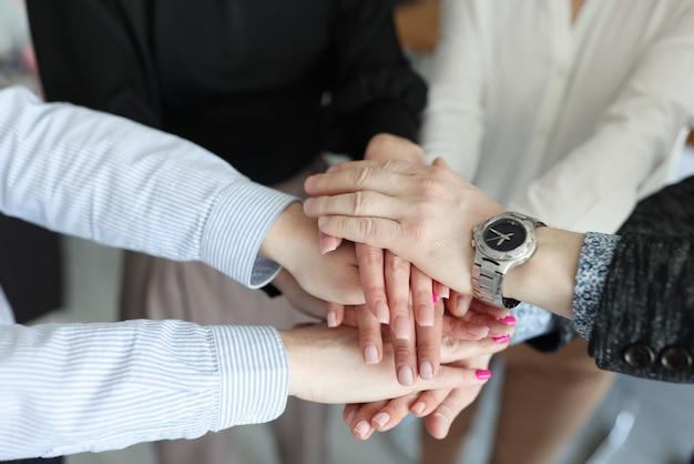 Zbliżenie wielu splecionych rąk biznesmenów w biurze
