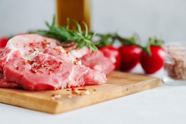 Zbliżenie wieprzowina niegotowane stosy z przyprawami i gałązką rozmarynu.