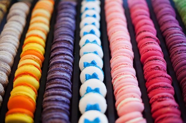 Zbliżenie wierszy i kolumn wielobarwnych macarons, tradycyjne francuskie ciasteczka.