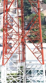 Zbliżenie wieży telekomunikacyjnej z białym i czerwonym kolorem i niebieskim niebem.