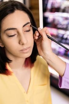 Zbliżenie wizażystka stosuje kosmetyk do pielęgnacji skóry hiszpanin kobieta w salonie piękności styl życia twarzy i dłoni, nakładanie makijażu za pomocą pędzla żółty kolor roku