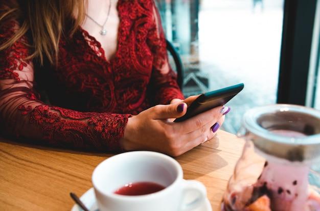 Zbliżenie wizerunek kobieta trzyma mądrze telefon w kawiarni i używa